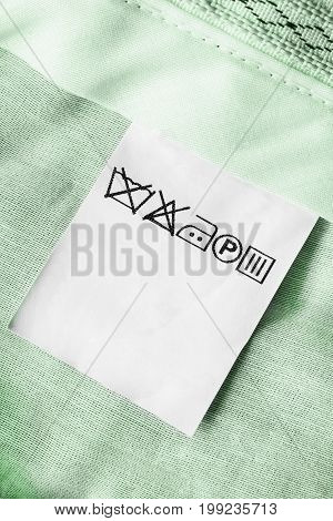 Washing instructions clothes label on green textile background