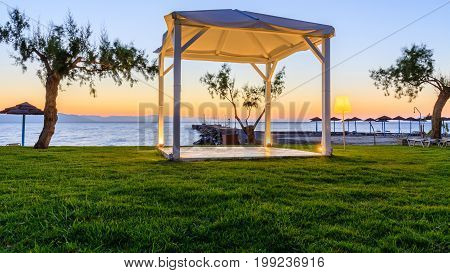 White wooden shed at seashore during sunrise.