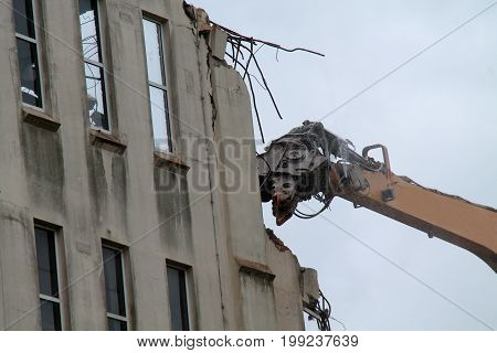 The Jaws of an Excavator Demolishing a Building.