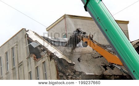 An Excavator Spraying Water as it Smashes up Concrete.