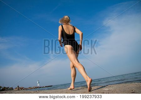 Woman running on the beach enjoying the sea view in clear blue sky with copy space