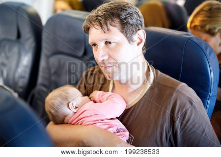 Young tired father and his sleeping baby daughter during flight on airplane going on vacations. Dad holding baby girl on arm. Air travel with baby, child and family concept.