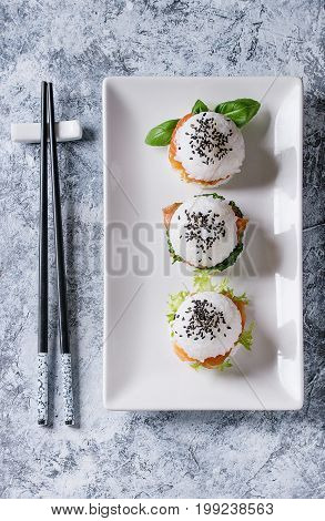 Mini rice sushi burgers with smoked salmon, green salad and sauces, black sesame served on white square plate with chopsticks over gray concrete background. Modern healthy food. Top view