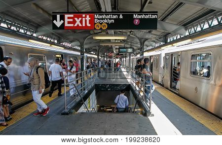 Queens New York August 10 2017: People move about the platform as they exit and enter trains at Queensboro Plaza subway station.
