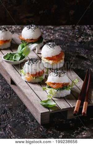Mini rice sushi burgers with smoked salmon, green salad and sauces, black sesame served on wood pallet tray with chopsticks over dark brown concrete background. Modern healthy food