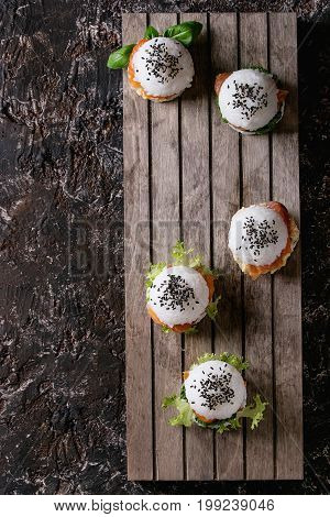 Mini rice sushi burgers with smoked salmon, green salad and sauces, black sesame served on wood pallet tray over dark brown concrete background. Modern healthy food. Top view