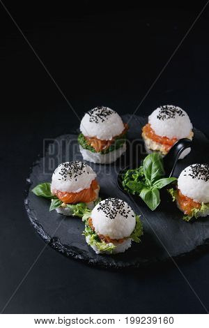 Mini rice sushi burgers with smoked salmon, green salad and sauces, black sesame served on slate stone board over black background. Modern healthy food