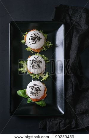 Mini rice sushi burgers with smoked salmon, green salad and sauces, black sesame served on black square plate with textile napkin over black background. Modern healthy food. Top view
