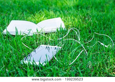 Open book and white smartphone with earphones lying on green grass on bright sunny summer spring day sunlight flecks relaxation modern technology learning education
