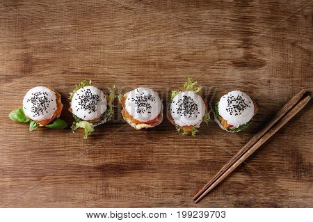 Mini rice sushi burgers with smoked salmon, green salad and sauces, black sesame served with wooden chopsticks over wood background. Modern healthy food. Top view with space