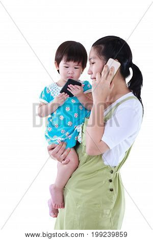 Busy Asian Mother Using Smartphone And Carrying Her Daughter.  Isolated On White Background.