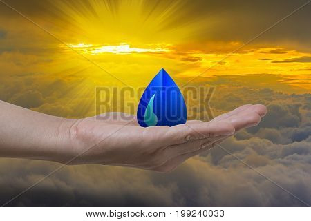 Water droplet in hand on white cloud with sunlight. Concept save water