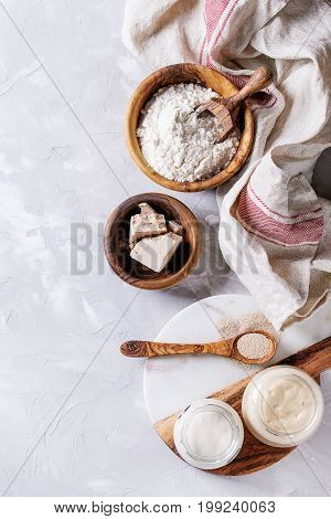 Rye and wheat sourdough in glass jars, fresh and instant yeast, olive wood bowl of flour for baking homemade bread. With spoon, serving board, kitchen towel over gray concrete background. Top view