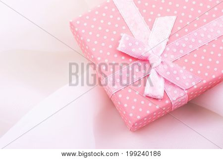 Pink gift box tied with satin ribbon with bow on delicate white fabric background romantic valentine mother's day Christmas present template copy space poster