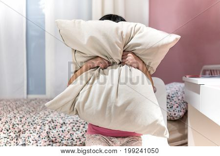 Depressed kid covering her face with pillow and screaming in anger in her room