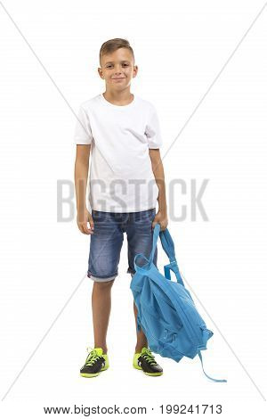 A teen pupil standing and holding a big blue bag isolated on a white background. A young teen with dark blond hair in a white t-shirt. An adorable little schoolboy with a bag of books.