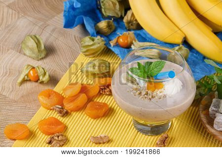 Beautiful composition of a spacious glass full of sweet smoothie with dried apricots physalis on a multi-colored background. Nutritious walnuts and orange apricots, yellow bananas for a snack.