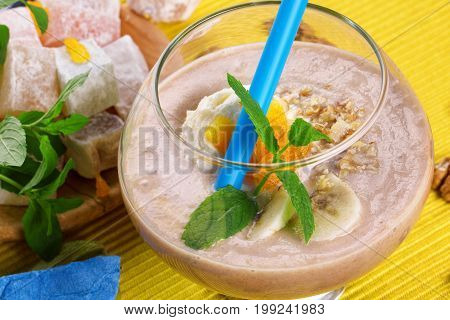 Close-up of a transparent glass of cold milkshake with mint, apricots and a blue straw on a yellow fabric background. Bright, sweet turkish delight and a fruity drink. Cocktails for summer parties