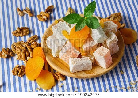 Close-up of sweet turkish delight, lokum or rahat lokum, vivid orange dried apricots, succulent green leaves of mint lying in a wooden plate on a striped background.