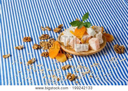 Closeup of turkish delight, lokum or rahat lokum, freah leaves of mint, bright dried apricots on a wooden plate, walnuts, crumbs of walnuts on the table on a striped background.