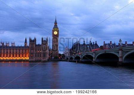 Big Ben and the House of Parliament of UK viewed from the opposite side of River Thames along with Westminster Bridge at night