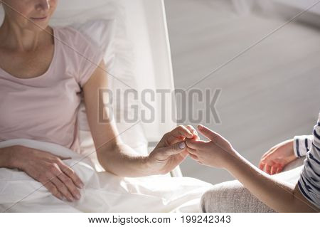 Sick Woman Touching Her Child Hand