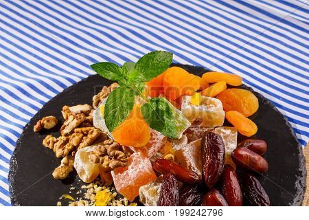 Close-up of a glass plate with turkish delight, locum or rahat lokum on it, walnuts, date fruits or dates and vivid leaves of mint on a striped background.