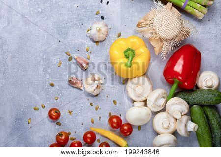 A view from above on yellow and red bell peppers, mushrooms, garlic, tomatoes, cucumbers, and spickles. Fresh ingredients for healthy dinner dishes. Cooking concept. Copy space. Still life.