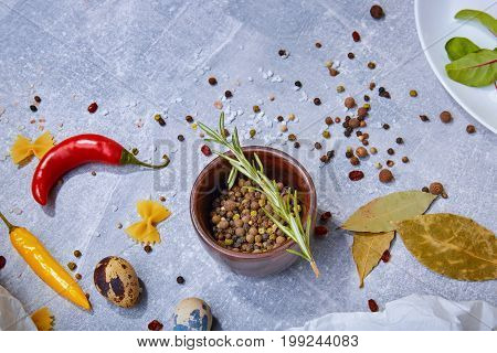 A view from above on fragrant ingredients. Seasoning on a gray stone background. A wooden bowl full of colorful spices next to bay leaves and bright chili peppers. Flavoring for taste. Copy space.