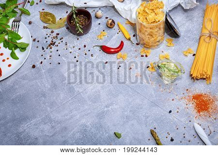 A view from above on a beautiful variety of pasta on a gray stone background. Different kinds of perfectly organized macaroni, a white plate, olive oil, red hot chili pepper, spices. Copy space.