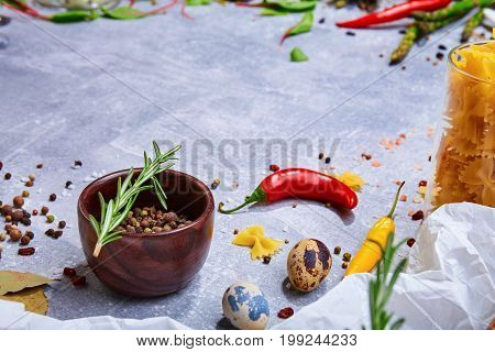 A close-up picture of ingredients. Seasoning on a gray stone background. A wooden bowl full of colorful spices next to bay leaves and particolored chili peppers. Flavoring for taste. Copy space.