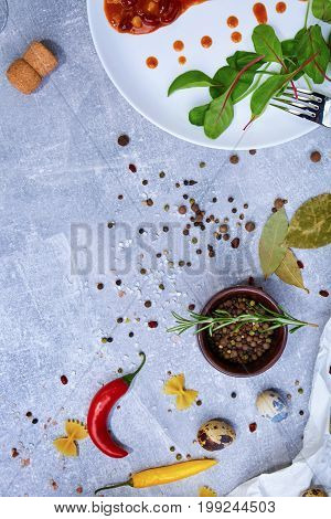 A top view of flavoring ingredients. A dish on a gray stone background. A wooden bowl full of colorful spices next to bay leaves and particolored chili peppers. Flavoring for taste. Copy space.