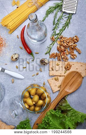 A view from above on supper ingredients. Stuffed olives, a glass bottle of water, salad leaves, bread, walnuts, rosemary, red hot chili pepper, pasta, quail eggs, spices and tableware. Food preparation.