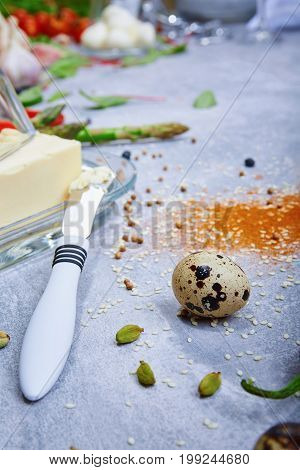 A close-up picture of breakfast ingredients. A glass container for butter next to a metal butter knife o a gray table background. Spices and quail egg. Green raw asparagus. Food preparation.