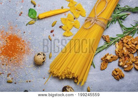 A view from above on a beautiful variety of pasta on a gray stone background. Different kinds of perfectly organized macaroni, walnuts, yellow hot chili pepper, rosemary herbs, and red spices.