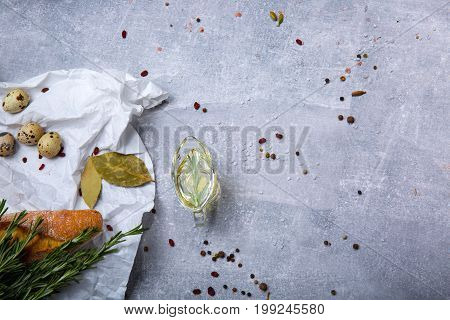 A view from above on food products on a grease-proof paper. Little quail eggs, baguette, dry bay leaves, rosemary twigs next to an oil tank. Food ingredients on a gray table background. Copy space.