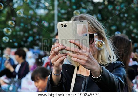 Moscow Russia - August 01 2015: Woman takes photos with her phone on a background of soap bubbles at the festival