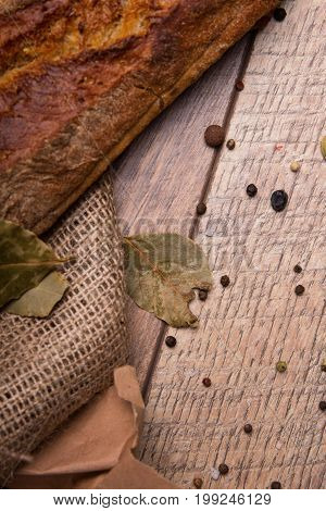 A close-up picture of a crunchy, crusty, traditional french baguette on a rustic wooden background. Top view of a dry bay leaf and black round peppers with a dark brown baked pastry.
