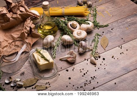 A view from above on a piece of butter in a glass container on a wooden table background. Garlic, mushrooms, rosemary twigs, yellow noodles with olive oil next to a brown cooking paper. Italian pasta.