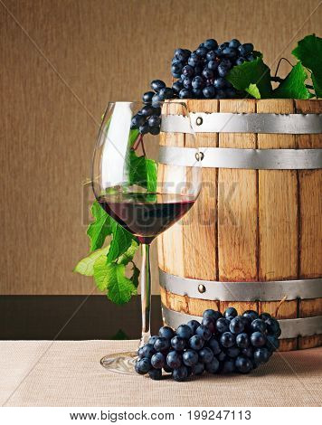 Wooden Wine Barrel And Glass Of Red Wine On Table