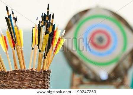 Archery concept. Basket with arrows in front of target.
