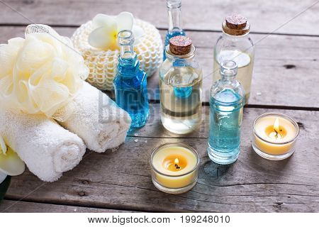 Wellness setting in blue yellow and white colors. Bottles wih essential aroma oil towels candles and wisps on wooden background. Selective focus.