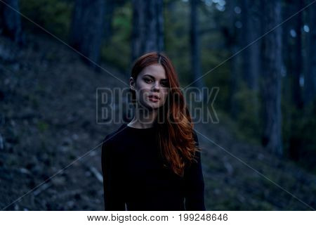 Beautiful young woman in a black dress in a dark forest.