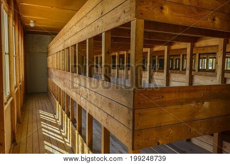 Dachau Concentration Camp Germany - August 29 2015: Inside sleeping quarters with wooden bunk beds from barrack room showing terrible prisoners living conditions from extermination camp.