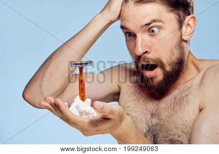 A man with a beard on a blue background holds a razor and shaving foam, portrait, emotions.