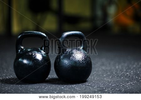 A close-up picture of two metal black kettlebells used perform ballistic exercices. Sports equipment on a blurred background. Kettlebell on a gym ground. Sports, health, workout concept.