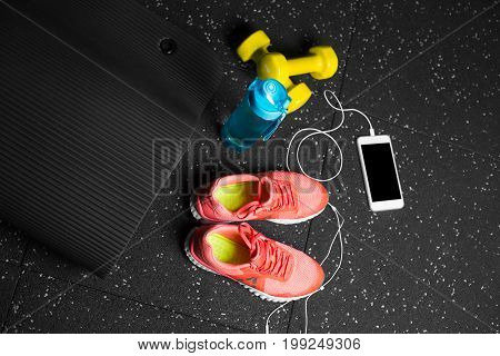 A view from above on sportive accessories for gym training on a black background. Blue sportive bottle, orange training shoes, yellow dumb-bells, black pilates mat. Training concept.