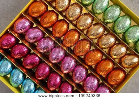 Chocolate Easter eggs in colorful foil. Sweet food.
