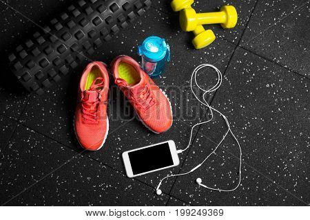 A view from above on blue sportive bottle, orange training shoes, yellow dumb-bells, black pilates mat and modern phone with headphones on a black background. Training, sports concept. Copy space.