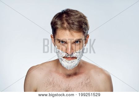 Man with beard on white isolated background in shaving foam, portrait.